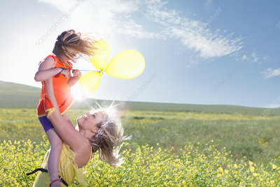 Sisters playing in field of flowers