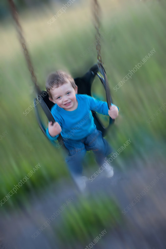 Blurred view of boy swinging