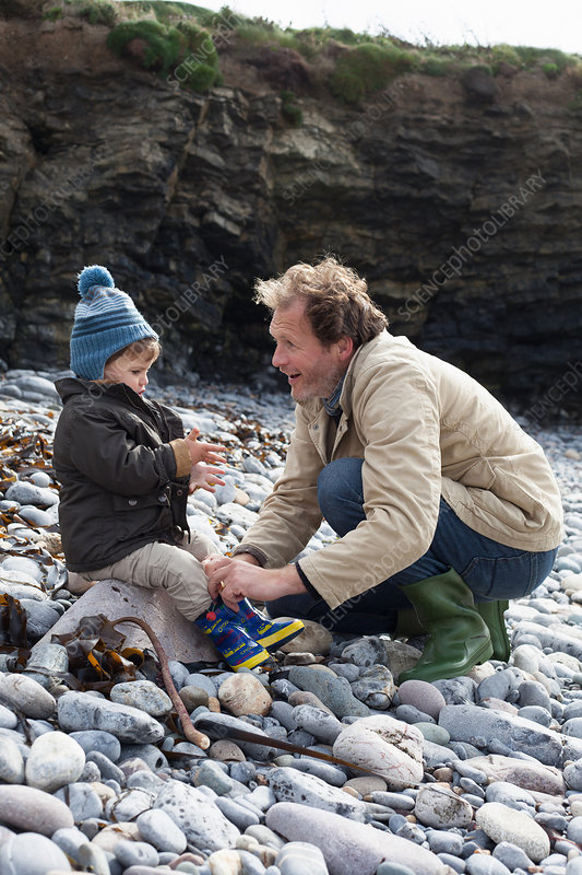 Father and son playing on rocky beach