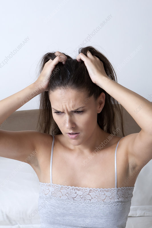 Woman scratching her head in bed