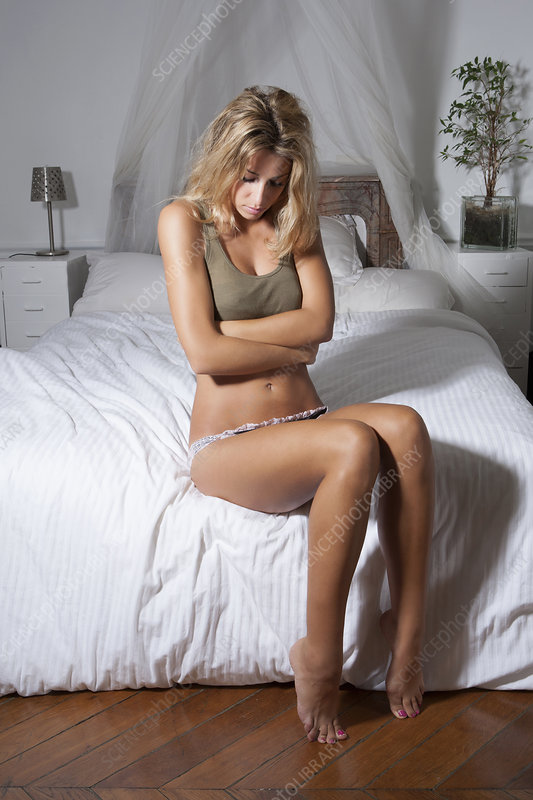 Woman clutching her belly on bed