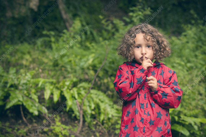 Girl holding finger over lips in forest