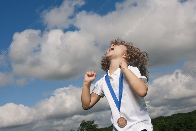 Girl with medal cheering outdoors