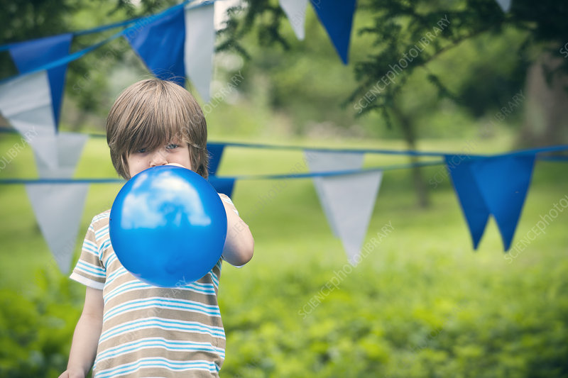 Boy blowing up balloon outdoors