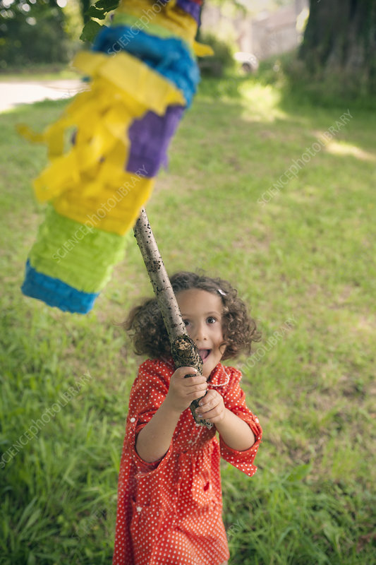 Girl swinging at pinata at party