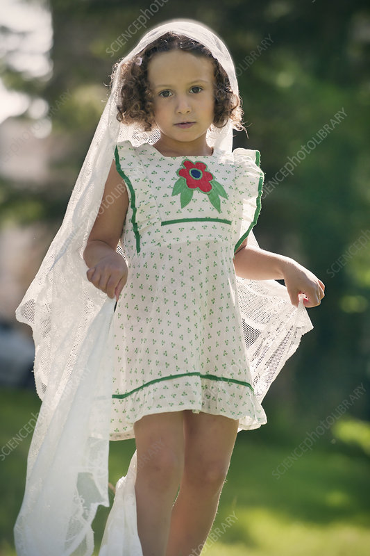 Girl playing with veil in garden
