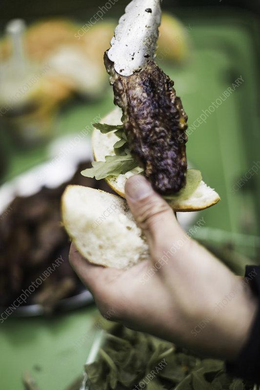 Hands placing sausage on bun