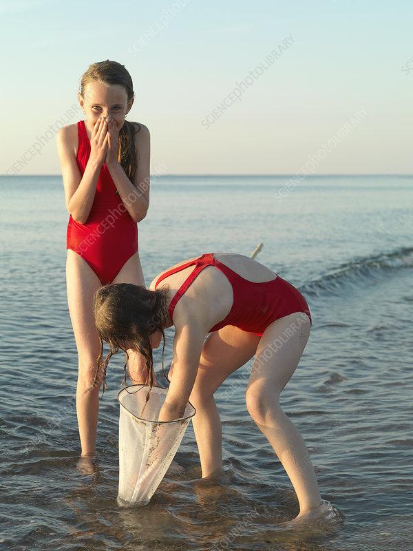 Girls fishing in shallow water