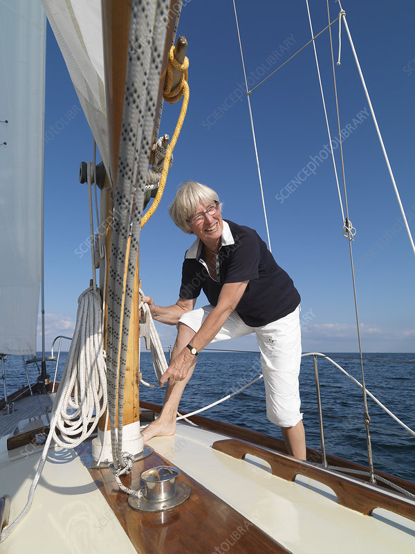 Woman adjusting rigging on sailboat