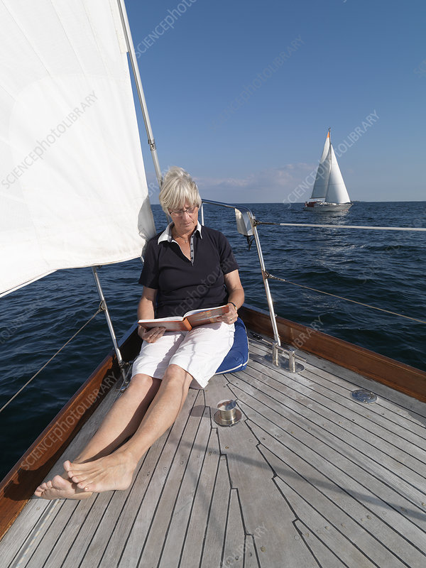 Older woman reading on sailboat