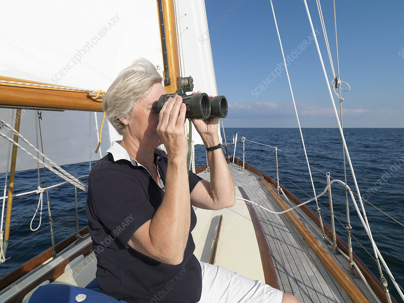 Older woman using binoculars on sailboat