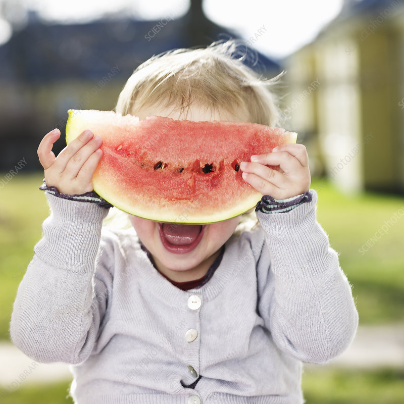 Toddler girl playing with watermelon