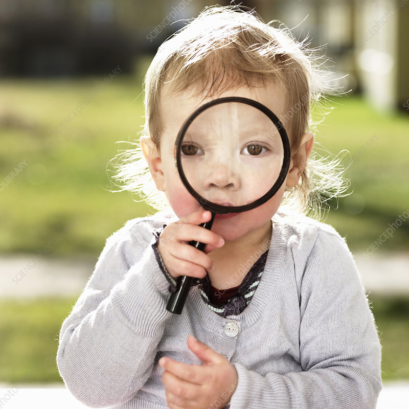 Toddler girl holding magnifying glass