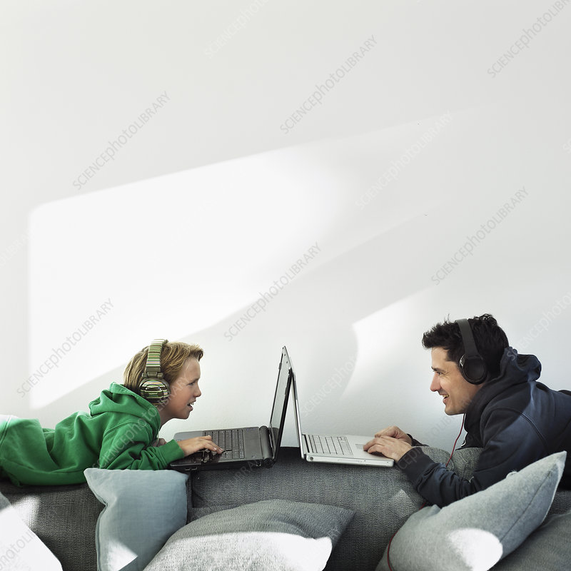 Father and son using laptops on sofa