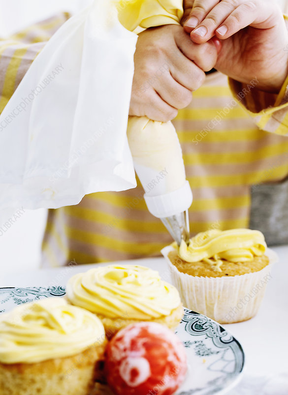Hands icing cupcake on table