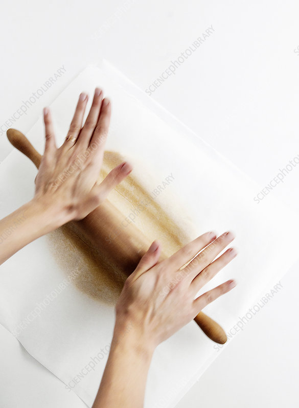 Hands rolling dough on counter