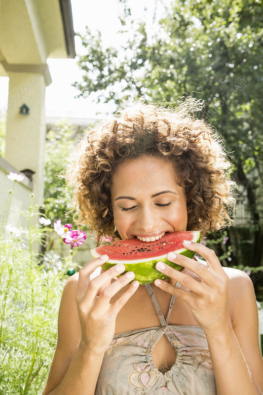 Smiling woman eating watermelon
