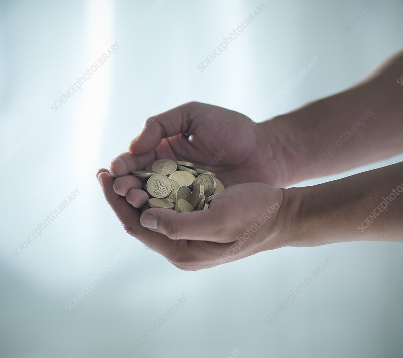Hands holding pile of coins