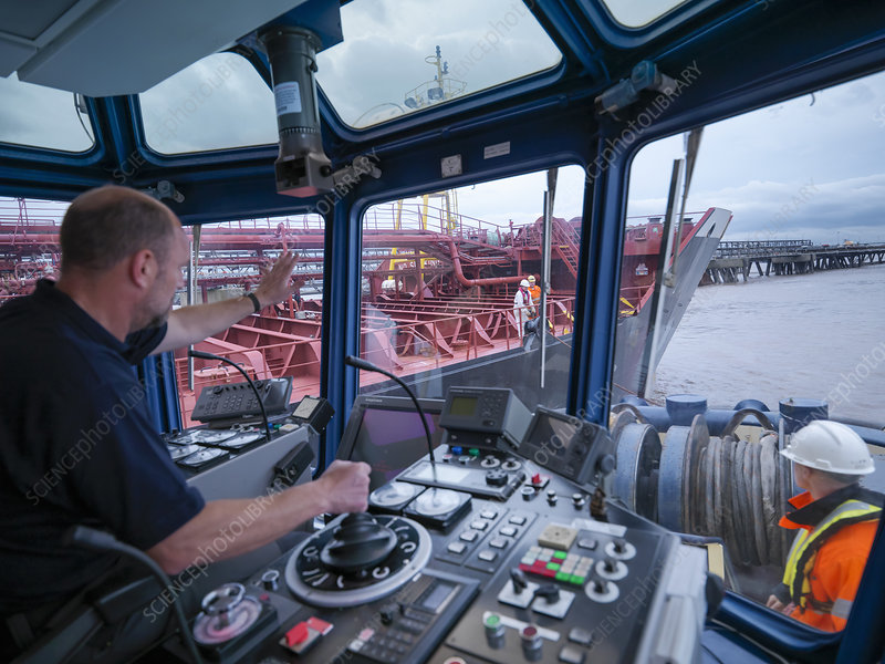 Worker driving tugboat in wheelhouse