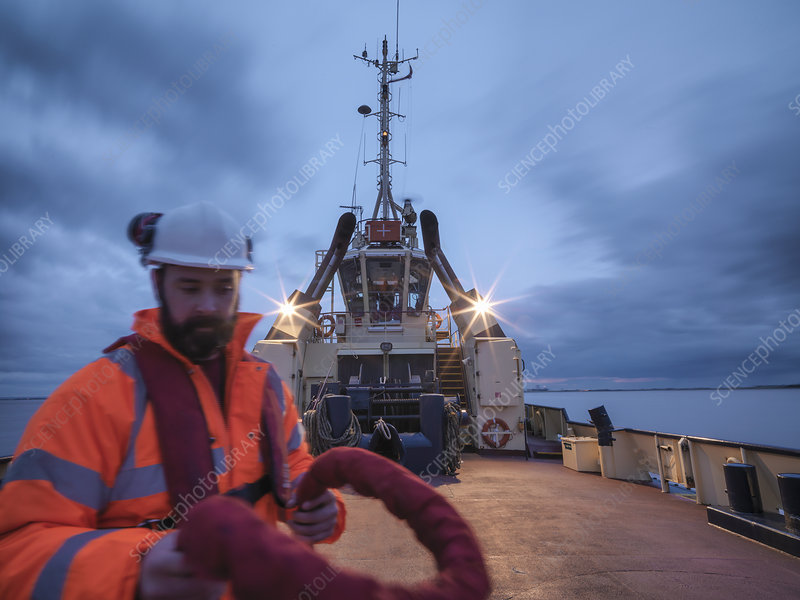 Worker holding rope on tugboat deck
