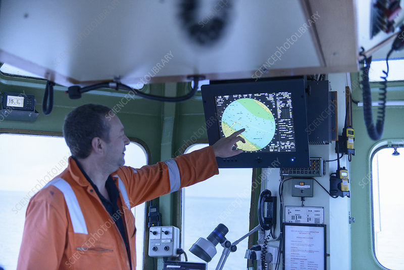 Tugboat worker examining map