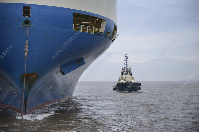 Tugboat sailing by large ship
