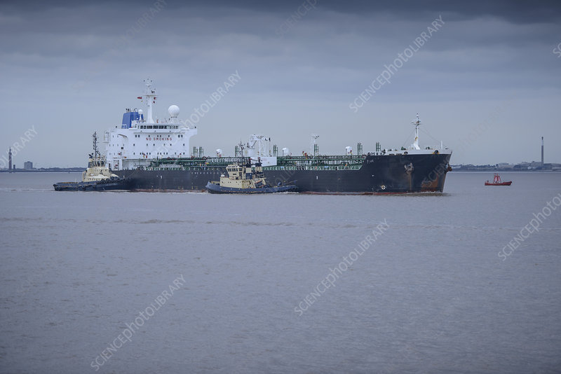 Tugboats pushing ship to harbour