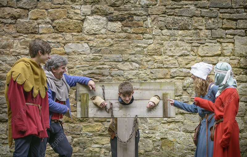 Students examining medieval stocks