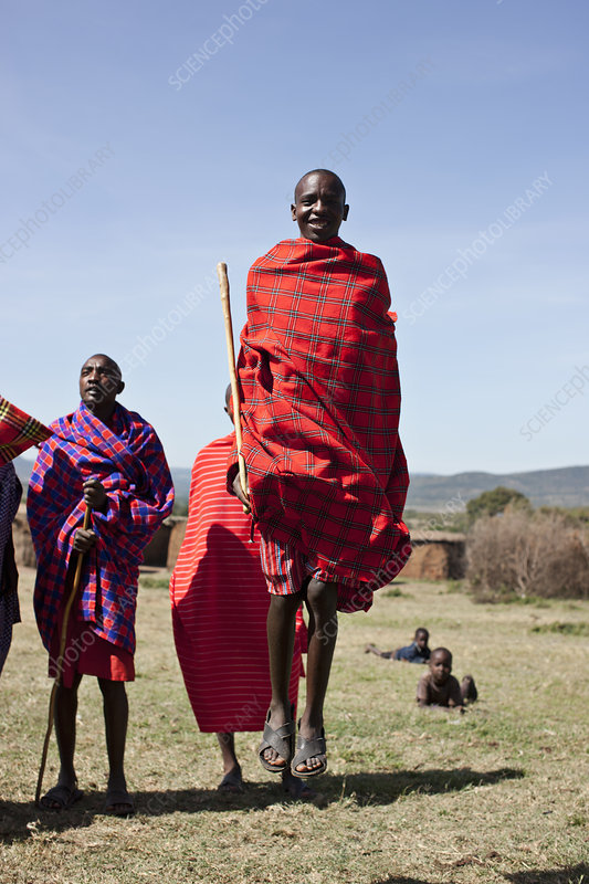 Maasai people walking in grassy field