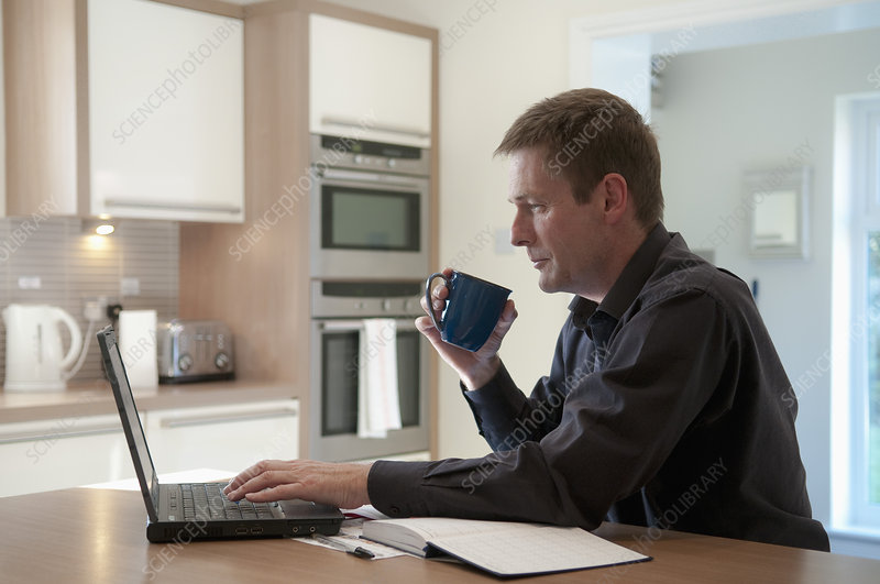 Businessman working on laptop in kitchen