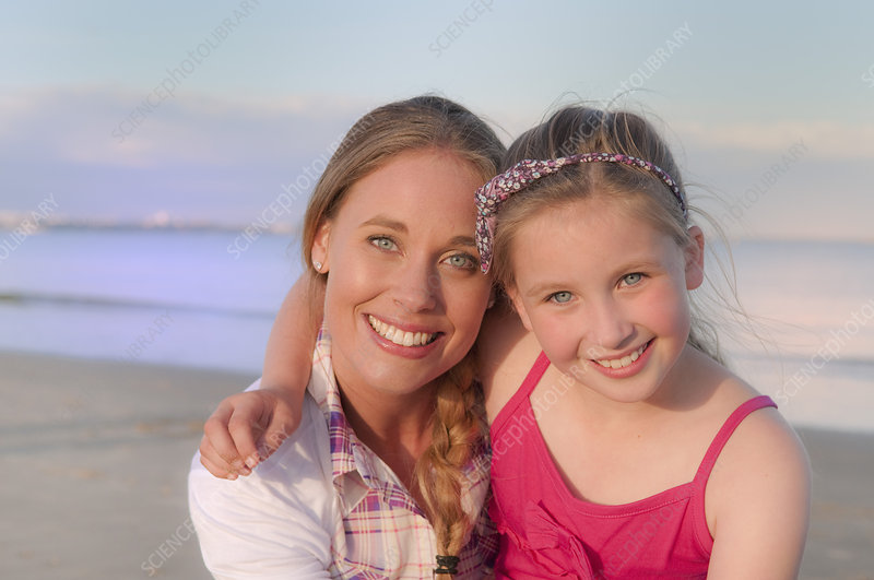 Mother and daughter smiling on beach