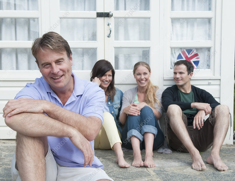 Man sitting with family outside house