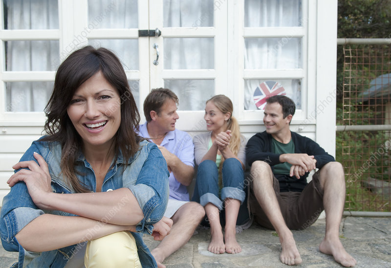 Woman sitting with family outside house