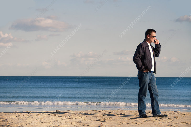 Man talking on cell phone on beach