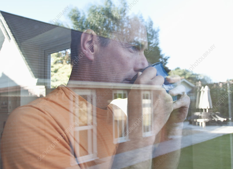 Man having coffee reflected in window