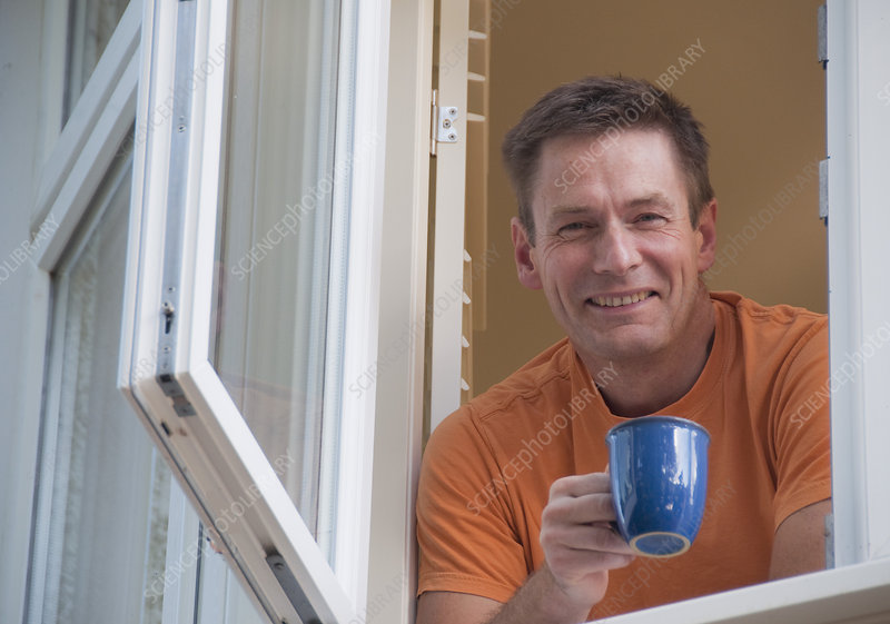 Man with coffee leaning out window