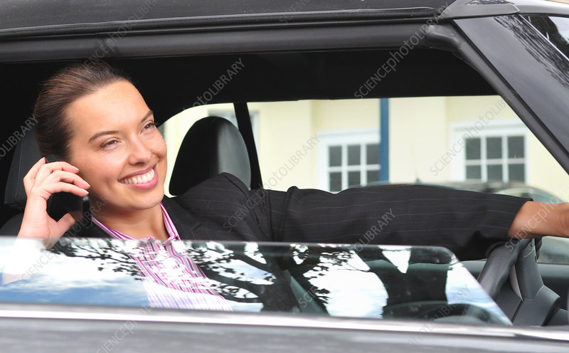 Businesswoman on cell phone and driving