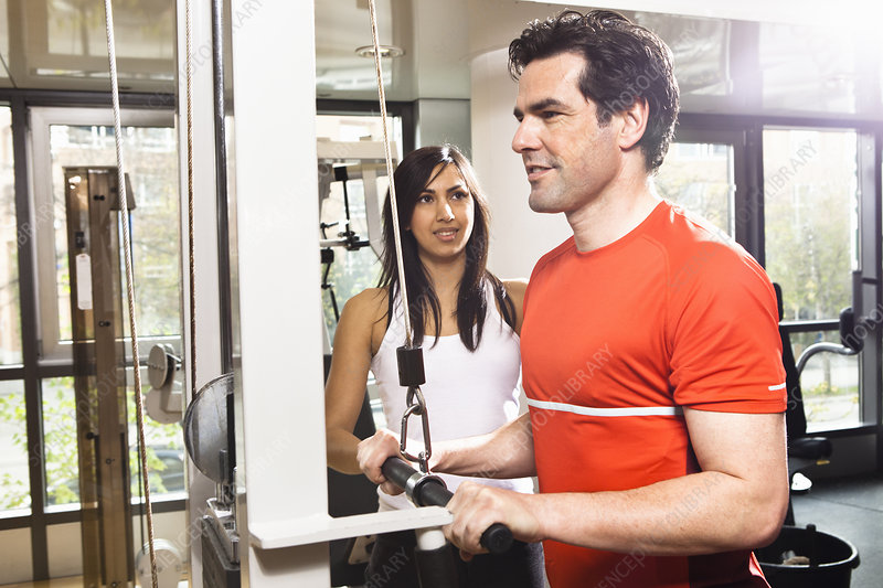 Man working with trainer at gym