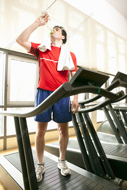 Man drinking water on treadmill at gym