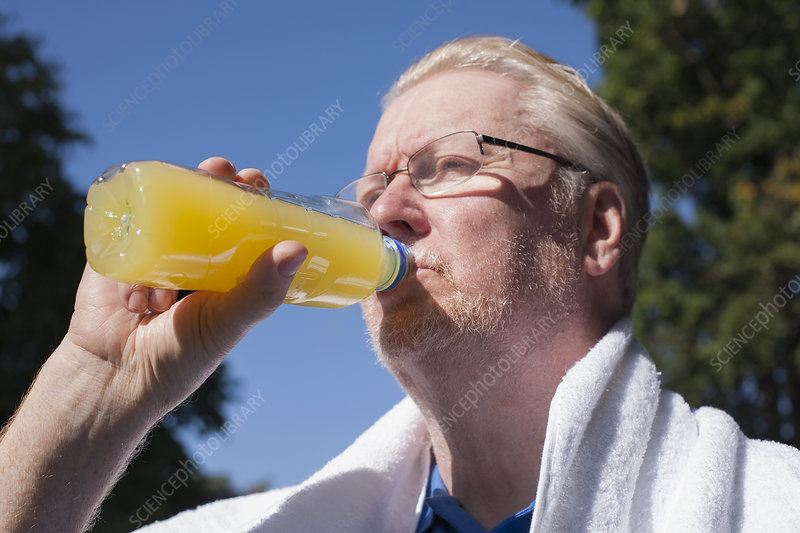 Older man drinking orange juice outdoors