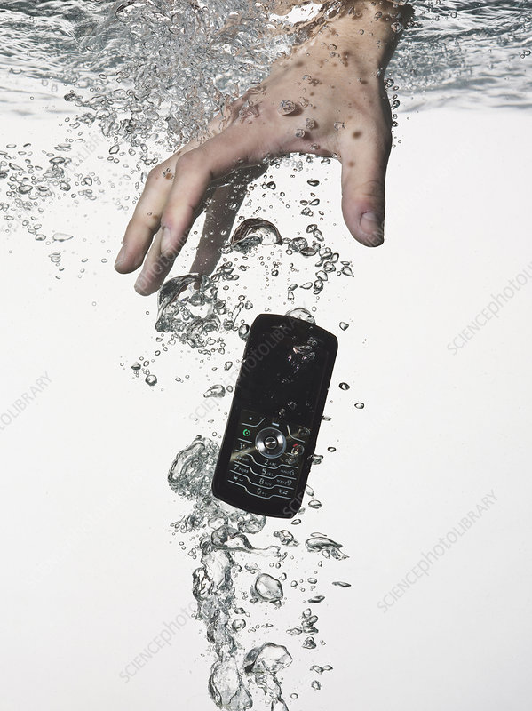 Hand grasping cell phone in water