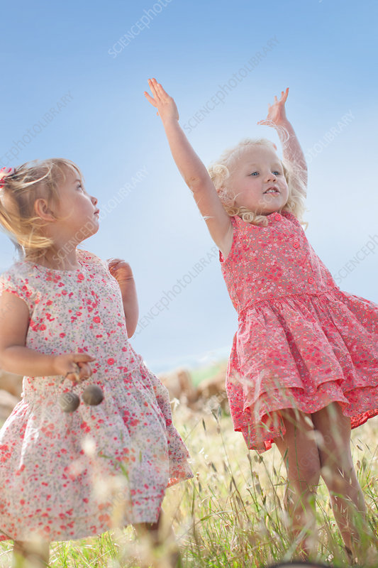 Girls playing in tall grass