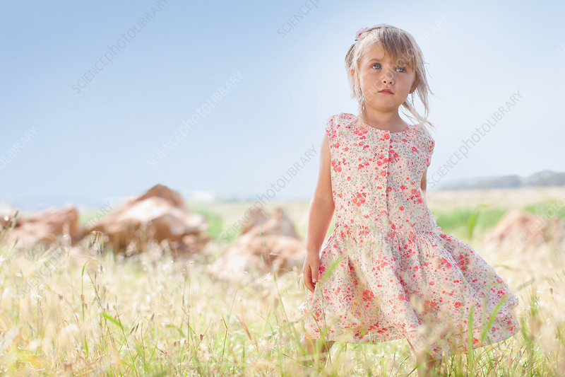 Girl standing in tall grass outdoors
