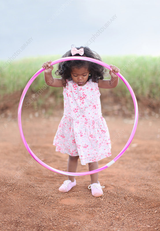 Girl playing with hula hoop on dirt road