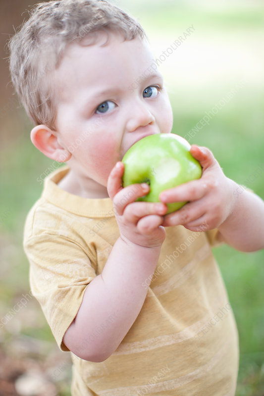 Boy eating apple outdoors