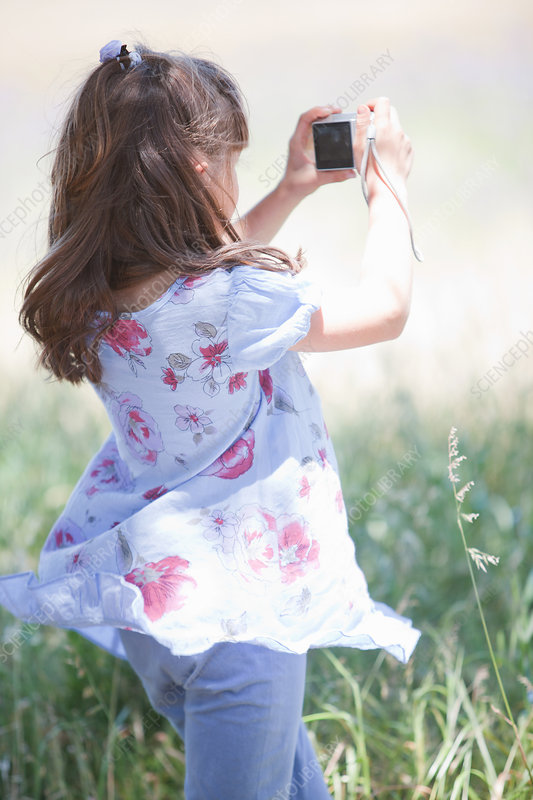 Girl taking pictures in tall grass
