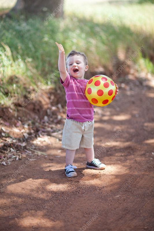 Toddler boy with ball on dirt road