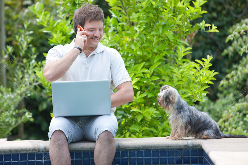 Man using cell phone and laptop outdoors