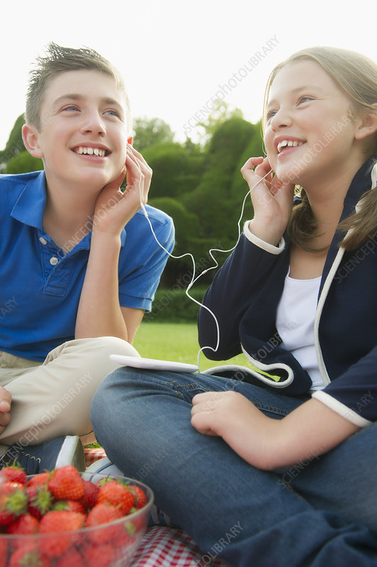 Children listening to earphones outdoors