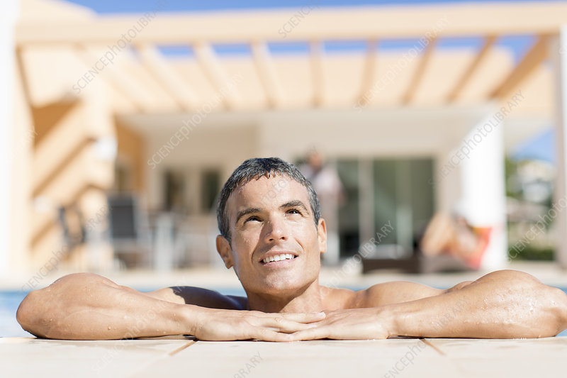 Man resting on edge of swimming pool